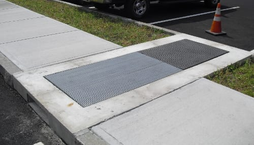 After installation, the unit is completed integrated with the sidewalk and the landscape bed.