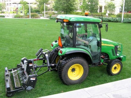 The author aerates Greenway lawns using a fracturing aerator attached to a tractor.