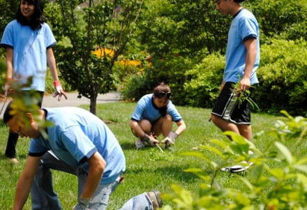 Volunteers enjoy a nice morning on the Greenway while helping hand weed a lawn.