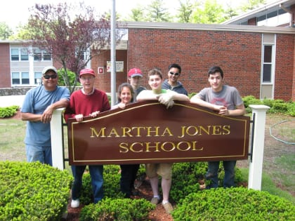 Sam Gantert (center) with a few of the volunteers who helped plant a butterfly garden at Martha Jones School.