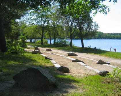 Lake Massapoag, 2015: An early summer day at a New England lake. Almost every New England town has a local recreational lake or pond. A goal of this project was to maintain the recreational value of the lakeside park, which is used enthusiastically by the community spring through fall for swimming, walking, biking, relaxing, and weekly outdoor concerts, while restoring natural, ecologically supportive elements such as tree groves, native buffer plantings, and native materials such as granite boulders.