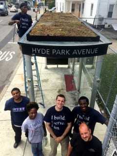 A YouthBuild Boston trainee waters in a green roof installed on one of Boston's bus shelters after installation by a team of volunteers from YouthBuild and the Hyde Park Green Team led by Trevor Smith, foreground.