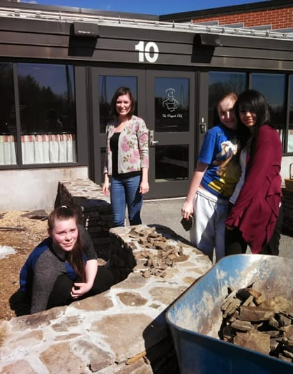 Erica Bradford, Cara Masson, Aislin Boyden, and Tyra Mitchell pick up stones after the construction of the Herb Garden wall.
