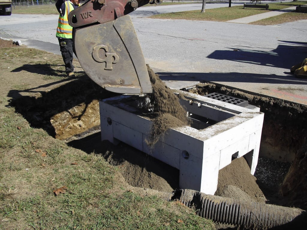 With the structure in place, the crew adds engineered soil media specifically designed to filter pollutants from the stormwater. Note that the media extends beyond the frame allowing for additional infiltration of treated water and unrestricted tree root growth.
