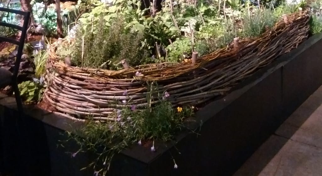 Recycled yard waste becomes wattle beds housing herbs and greens.